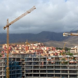 Construction with construction cranes in the background of the volcano on the island of Tenerife, Spain.