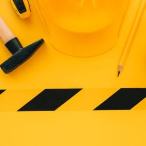 Under construction concept with yellow protective helmet and tools, top view flat lay minimalistic composition